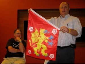 John Niggley shows the Östergötland banner of arms while Mike Hale looks on.