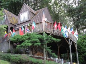 International flags fly from the home of Bill Hilliard, retired editor of The Oregonian, as mementos of his global travels advancing press freedom.