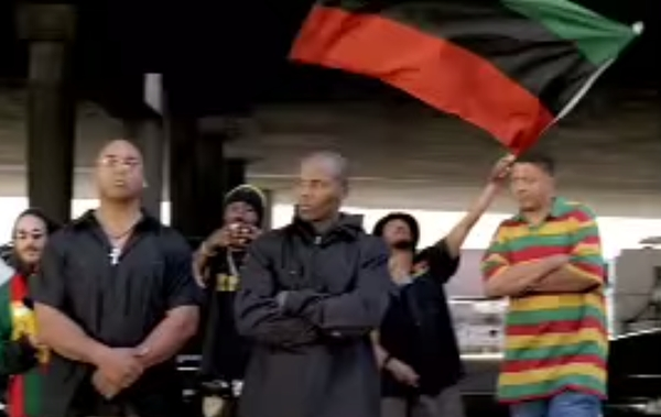 Waved in the background: the red, black, and green Pan-African flag.