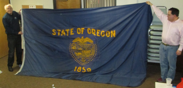 Michael Orelove and Scott Mainwaring stretch out an 8' x 12' Oregon state flag.