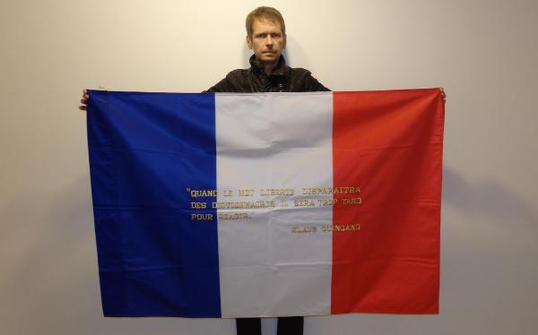 """Klaus Guingand and his flag with the sentence in French"""