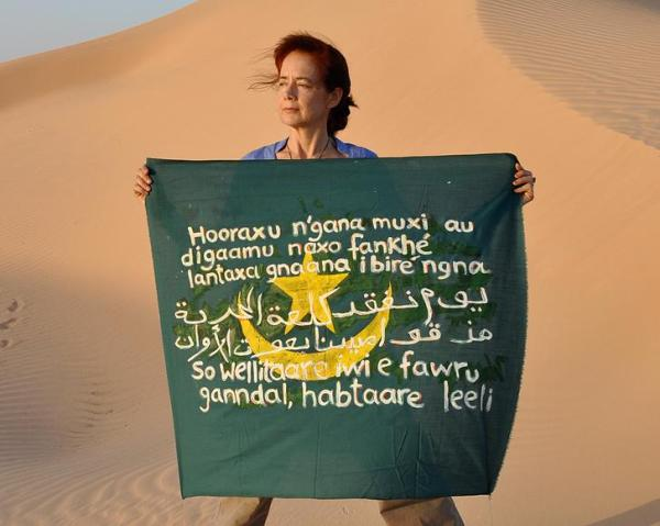 """Isabel Fiadeiro and her flag with the sentence in Pulaar, Arabic and Wolof."""