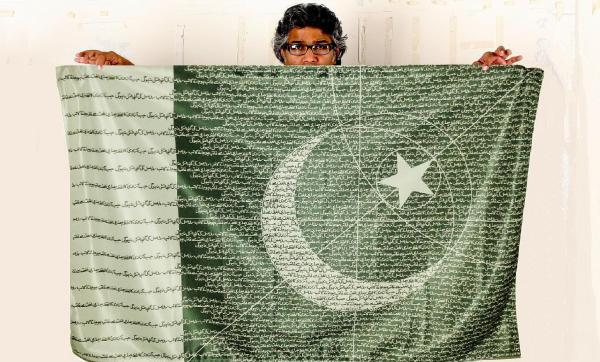 R.M Naeem and his flag with the sentence in Urdu.