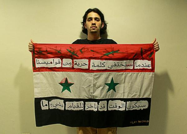 """Alaa Shasheet and his flag with the sentence in Arabic."""