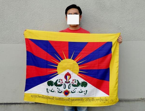 """Tenzin Tondup and his flag with the sentence in Tibetan."" (Tondup is a refugee in Nepal.)"