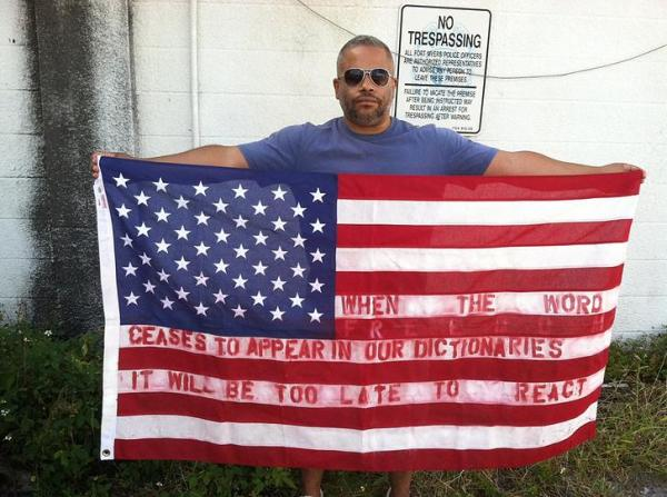 """Marcus Jansen and his flag with the sentence in American."""