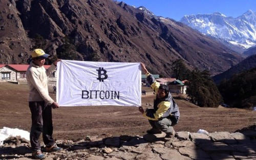"Allex Ferreira, a ""Brazilian Bitcoin enthusiast"" poses with a Bitcoin flag he plans to unfurl on the summit of Mt. Everest.  From cryptohoot.com."