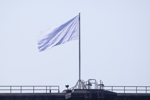 One of two enormous, custom-made, all-white US flags flying above the Brooklyn Bridge.