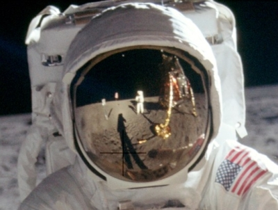 Detail of the original raw image, showing Armstrong reflected in Aldrin's visor.