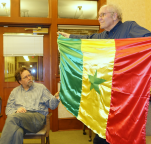 David Koski admires the Senegalese flag displayed by Michael Orelove.