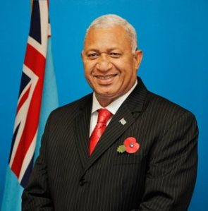 Fijian Prime Minister Frank Bainimarama in front of the current Fijian flag.