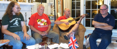 Casey Sims sings a song inspired by his new personal flag, enjoyed by Robert Izatt, Ken Dale, and Dennis Stephens.