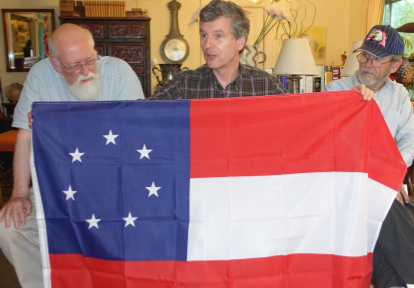 "At the July 2015 PFA meeting, Ted Kaye provides a summary of the flags of the Confederacy, displaying the first national flag, the ""Stars and Bars"" as John Schilke and Fred Paltridge look on."