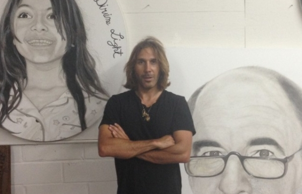 Nimai Kesten in front of some of his portraits, August 2013.  Photo from the Art Nerd Los Angeles blog.
