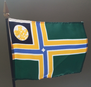 A stick flag showing the previous fdesign of Portland's flag, in (very limited) use 1970-2002.  A modification of Lynch's original design.