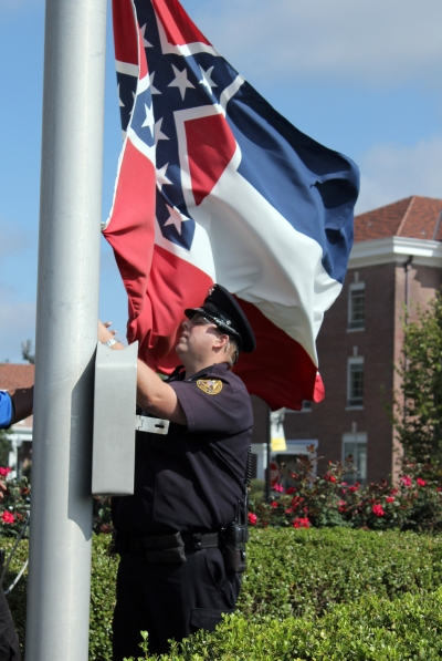 An SMU police officer takes down the state flag, 28 October 2015. Photo by Brittany Stewart, Student Printz.