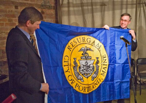 Portland City Councilor Ed Suslovic presenting the flag of the City of Portland